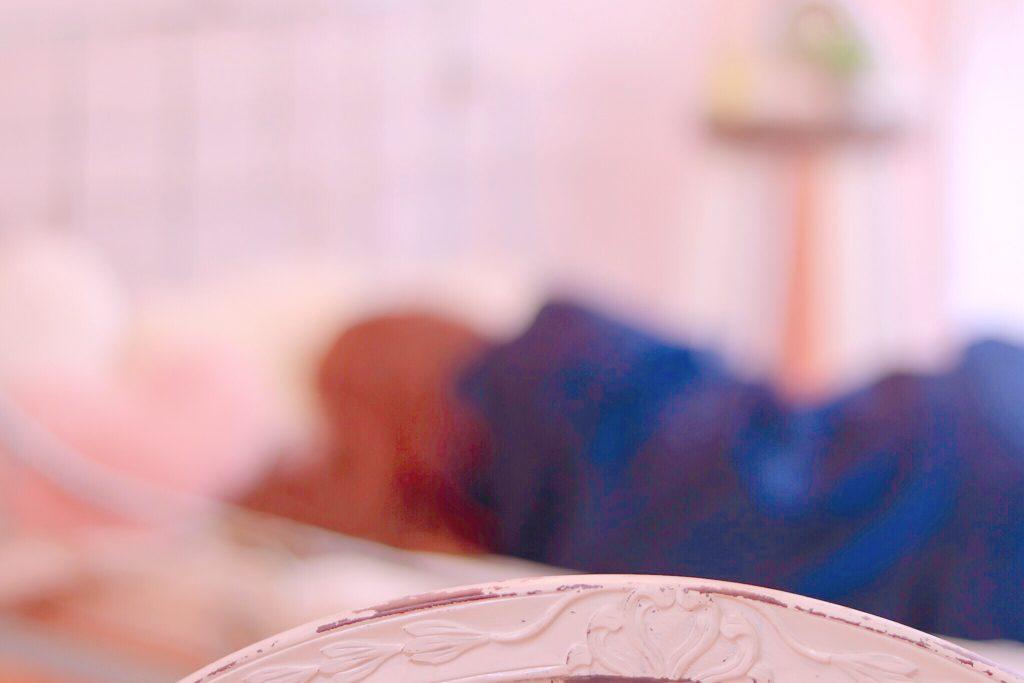 ベッドで横向きに寝ている女子