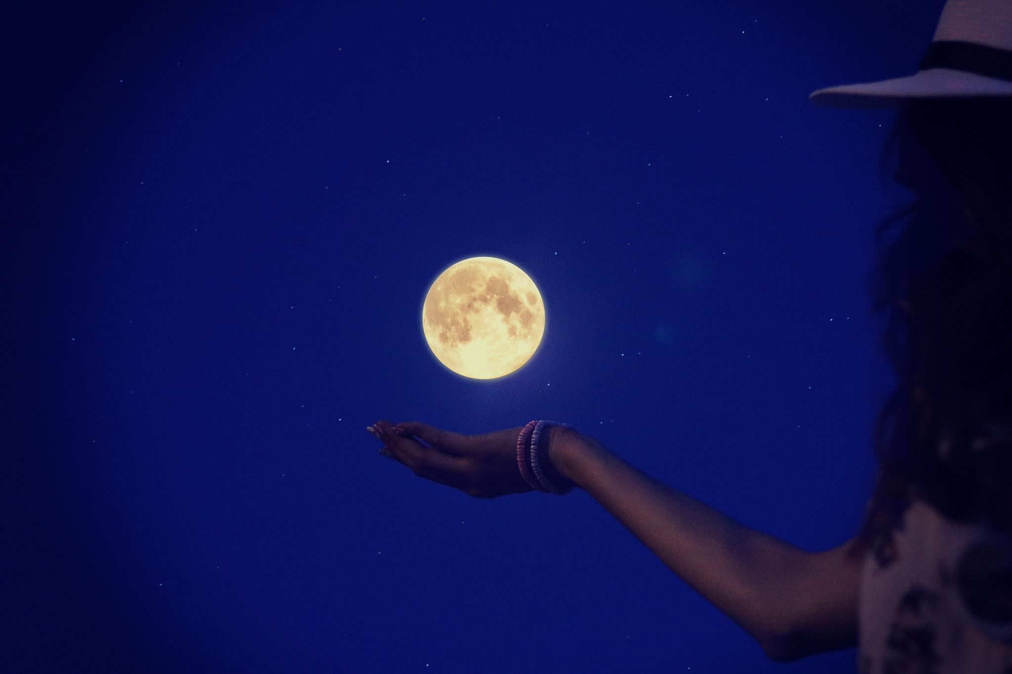 満月に手をかざす女の子